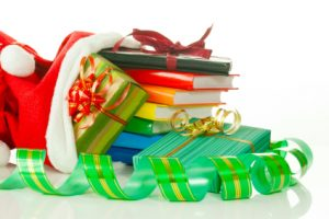 Christmas presents with e-book reader and books in bag against white background